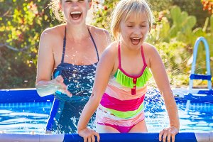 cheerful healthy mother and daughter in swimming pool playing