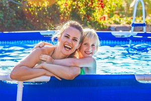 happy active mother and child in swimming pool embracing
