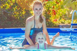 happy active mother teaching daughter to swim in swimming pool