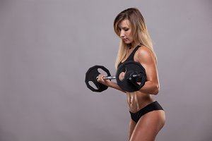 Beautiful athletic woman in sporty cloths is pumping muscles with a barbell, isolated on grey background with copyspace