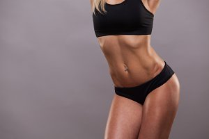 Beautiful athletic torso of woman in sporty cloths. isolated on grey background with copyspace