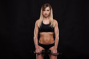 Beautiful fitness woman is lifting dumbbells. Sporty girl showing her well trained body. isolated on dark background with copyspace