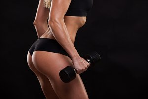Close up attractive athletic woman is pumping up muscles with dumbbells, back view isolated on dark background with copyspace
