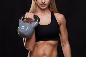 Young attractive fitness woman is doing exercise with a kettlebell workout. Sporty girl showing her well trained body. isolated on dark background with copyspace