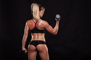 Attractive athletic woman is pumping up muscles with dumbbells, back view isolated on dark background with copyspace