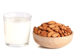 Almond milk in a glass and almonds in a wooden bowl isolated on a white background