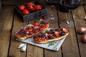 Wine appetizer set. Glass of red wine, brushettas with fresh tomato and jamon on over rustic grunge wooden background