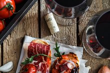 Variety of small sandwiches with jamon, tomatoes, parmesan cheese, fresh basil served with glass of red wine on wooden board, top view