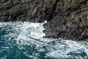 Swirling waves crashing on rocks