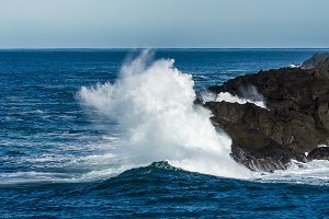 Wave crashing ashore on rocky beach
