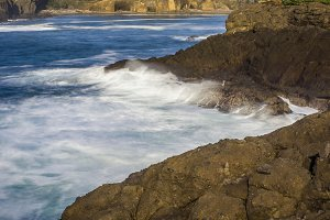 Waves breaking over dark rocks