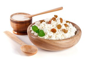 Cottage cheese with raisins in a wooden bowl isolated on a white background