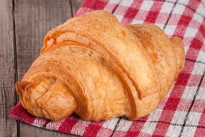 One croissant on a wooden table with a napkin