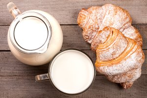 jug and glass of milk with croissants on a wooden background. Top view