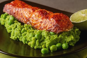 Grilled salmon with pea puree on a brown plate. Gray background.