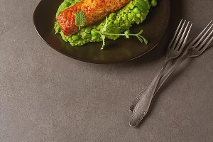 Grilled salmon pea puree decorated with mint on a brown plate. Gray background.