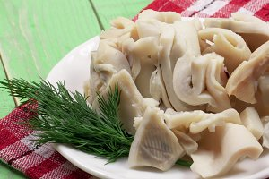 sliced squid on a plate on a green wooden background