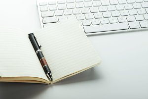 Open notepad and pen next to keyboard on white background.