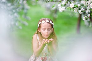 Cute girl in blooming apple tree garden enjoy the warm day