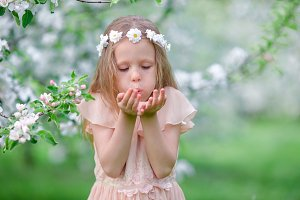 Portrait of beautiful little girl in blooming apple tree garden on spring day
