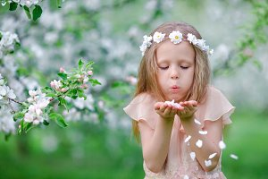 Adorable little girl in blooming tree garden on spring day