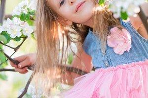 Beautiful little girl in blooming apple tree garden outdoor