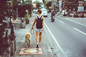 Woman walking with dog in the street