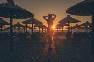 sexy woman walk on beach at sunset