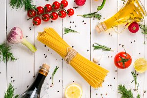Spaghetti, tomatoes cherry, olive oil, herb and spices on old white wooden background. Set for healthy foods. Ingredients for salad