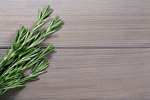 Organic bunch of fresh rosemary on the old grey wooden background. Free space for your text