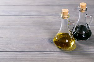 Organic fresh olive oil and soy sauce on the old grey wooden background. Free space for your text