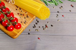 Spaghetti, tomatoes cherry, olive oil and spices on old gray wooden background