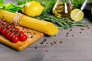 Spaghetti, tomatoes cherry, olive oil, herb and spices on old gray wooden background