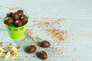 Beautiful Easter composition with chocolate eggs in the iron pail, colored powder for cakes and flowers on blue wooden background