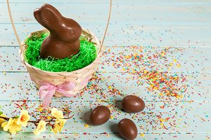 Beautiful Easter composition with chocolate bunny and eggs in a wicker basket with a bow, colored powder for cakes and flowers on blue wooden background