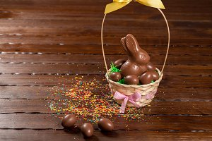Beautiful Easter composition with chocolate bunny and eggs in a wicker basket with a bow, colored powder for cakes on old brown wooden background