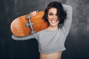 Beautiful Young sporty woman with skateboard
