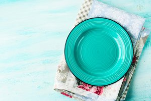 Green plate on Vintage napkin wooden textured background