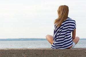 girl sitting on pier