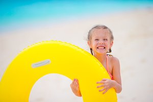 Little girl with inflatable rubber circle on white beach at caribbean vacation