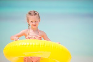 Little girl with yellow inflatable rubber circle going to swim in the ocean