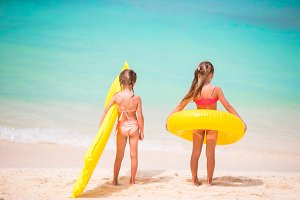Little girls going to swim on summer beach vacation