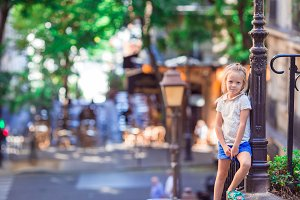 Adorable happy little girl outdoors in Montmartre. Portrait of caucasian kid enjoy summer vacation in Europe