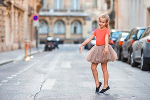 Adorable little girl during summer vacation in Paris. Amazing balerina enjoy her trip in France