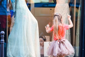 Adorable little girl outdoors in city of love watching beautiful wedding dresses