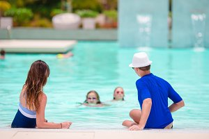 Happy family with two kids in outdoor swimming pool