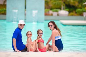 Family of four in outdoor swimming pool