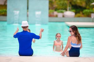 Happy family with two kids in outdoor pool