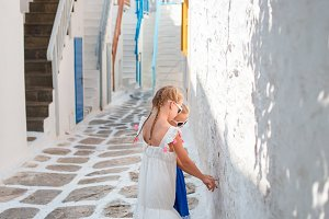 Cute little girls outdoors in narrow street at old city in Greece