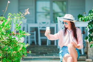 Young beautiful woman taking selfie with phone in outdoor cafe